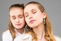 Апеллирующ безупречные девушки со светлыми волосами стоя близко друг к другу стоковое фото