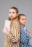 Апеллирующ длинн-с волосами сестры различных возрастов стоя спина к спине стоковые изображения
