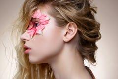 Апеллирующ модель имея розовые тушь и цветки около глаза стоковые фото