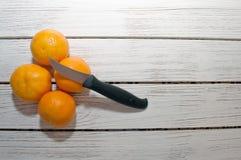 4 апельсина на белой столешнице с ножом Стоковое фото RF