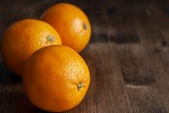 3 апельсина на темной деревянной предпосылке стоковые изображения rf