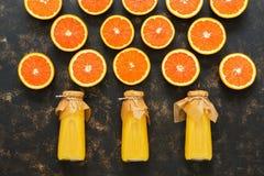 Апельсиновый сок и половины апельсина на темной предпосылке, взгляд сверху Стоковые Изображения