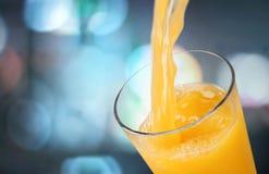 Апельсиновый сок лить на запачканной предпосылке Стоковое фото RF