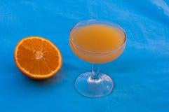 Апельсиновый сок на голубой предпосылке стоковые изображения