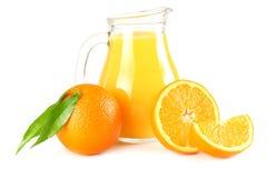 Апельсиновый сок при оранжевые и зеленые лист изолированные на белой предпосылке сок в кувшине Стоковые Фото