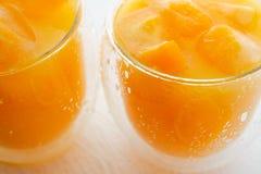 Апельсиновый сок с кубами льда в стеклах закрывает вверх Кубы льда с небольшими частями замороженных апельсинов стоковое изображение