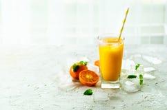Апельсиновый сок с льдом и tangerines на белой предпосылке Открытый космос для вашего текста Copyspace Холодный напиток для горяч Стоковое Изображение RF