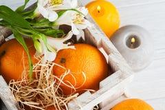 Апельсины в деревянной коробке, освещенной свечи Стоковые Изображения