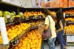 Апельсины покупки женщины от плодоовощ кладут на полку в магазине Стоковые Изображения RF