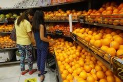 Апельсины покупки женщины от плодоовощ кладут на полку в магазине Стоковые Фото