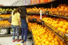 Апельсины покупки женщины от плодоовощ кладут на полку в магазине Стоковые Изображения