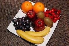 Апельсины, яблоки, виноградины, кивиы, вишни, бананы на белой плите на к стоковые изображения rf