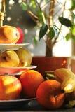 Апельсины яблок груш теплого цвета sunlit и плодоовощи бананов на сервере стойки фарфора 3 ярусов рядом с горшечным растением фик Стоковое фото RF