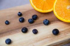 Апельсин и голубики на деревянной разделочной доске стоковая фотография