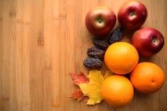 Апельсин и яблоки на бамбуковой предпосылке в стиле осени стоковая фотография