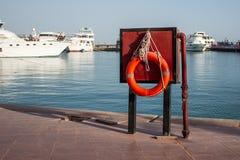 Апельсин lifebuoy на пристани на предпосылке яхт около моря Безопасность на воде и спасении от тонуть стоковая фотография