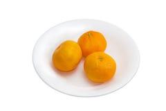 3 апельсина мандарина на белом блюде Стоковое Изображение RF