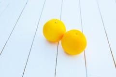 2 апельсина на белом деревянном столе Стоковая Фотография