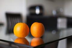 2 апельсина на стеклянном столе Стоковое фото RF