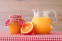 Апельсиновый сок, варенье, половины апельсина на красной checkered скатерти Стоковая Фотография RF