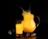Апельсиновый сок в прозрачном кувшине на черной предпосылке Стоковое Изображение RF