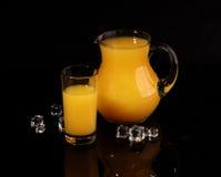 Апельсиновый сок в прозрачном кувшине на черной предпосылке Стоковое Фото