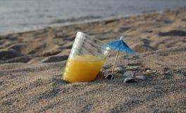 Апельсиновый сок в стекле на песке Стоковое Изображение