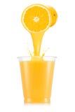 Апельсиновый сок лить вне от плодоовощ в пластичную чашку Стоковые Фотографии RF