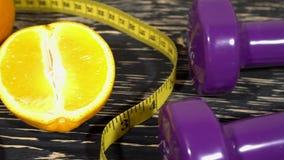 Апельсины, гантели и измеряя лента на деревянной предпосылке видеоматериал