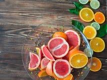 Апельсины, известки, tangerines и грейпфрут в шаре на темной деревянной предпосылке Взгляд сверху с космосом экземпляра Стоковая Фотография
