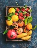 Апельсины, лимоны, гранатовое дерево, бананы, клубники и хурма в деревянной коробке Стоковое фото RF