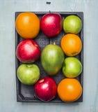 Апельсины, манго, яблоки различных разнообразий в конце взгляд сверху предпосылки деревянной коробки деревянном деревенском вверх Стоковые Фотографии RF