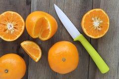 Апельсины мандарина и акриловый нож помещенные на старом деревянном floo Стоковые Фото