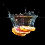 Апельсин, грейпфрут брызгая в воду стоковые фото