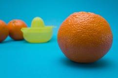 Апельсин и juicer на голубой предпосылке Стоковые Фотографии RF