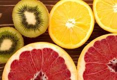 Апельсин кивиа грейпфрута в отрезке на деревянной предпосылке Стоковое Фото