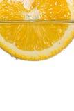 Апельсин куска в воде на белой предпосылке Стоковые Фото
