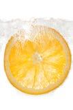 Апельсин куска в воде на белой предпосылке Стоковые Фотографии RF