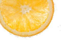 Апельсин куска в воде на белой предпосылке Стоковые Изображения RF
