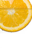 Апельсин куска в воде на белой предпосылке Стоковые Изображения