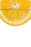 Апельсин куска в воде на белой предпосылке Стоковая Фотография RF