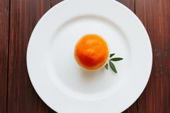 Апельсин на белой круглой плите с зелеными лист Стоковое Фото