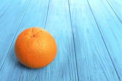 Апельсин на голубой таблице Стоковые Фото