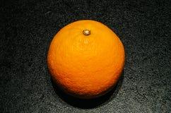 Апельсин на текстурированной черной предпосылке Стоковая Фотография RF