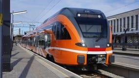 Апельсин покрасил региональный поезд ждать на следе в главном вокзале Таллина, Эстонии Стоковые Изображения RF