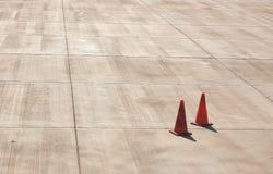 Апельсин 2 сигнализирует конусы дороги на конкретной плоской доске авиапорта с Стоковое Изображение