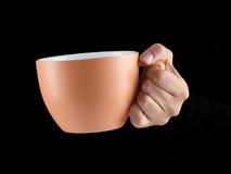 Апельсин - чашка цвета абрикоса - кружка на черной предпосылке Стоковые Фото