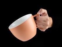 Апельсин - чашка цвета абрикоса - кружка на черной предпосылке Стоковое Изображение RF