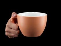 Апельсин - чашка цвета абрикоса - кружка на черной предпосылке Стоковое Изображение
