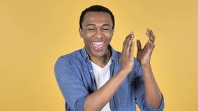 Аплодируя африканский человек, хлопающ, желтая предпосылка